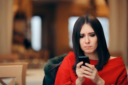 Mujer estresada leyendo un mensaje de texto en el teléfono inteligente