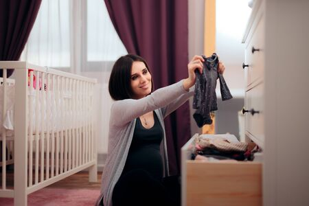 Happy Pregnant Woman Arranging Baby Clothes in a Drawer