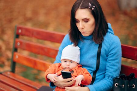 Mother and  Baby Checking Smartphone in The Park