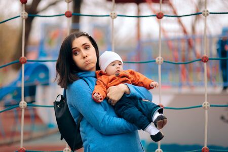Tired Exhausted Mother Holding her Baby on a Playground