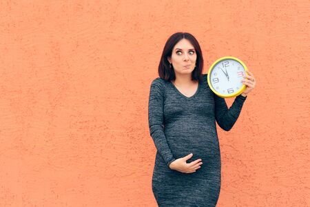 Cheerful Girl Holding a Clock Awaiting her Baby