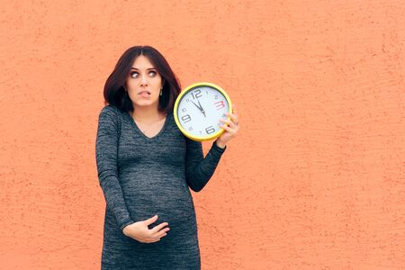 Worried Pregnant Woman Holding a Clock Awaiting her Baby Stock Photo