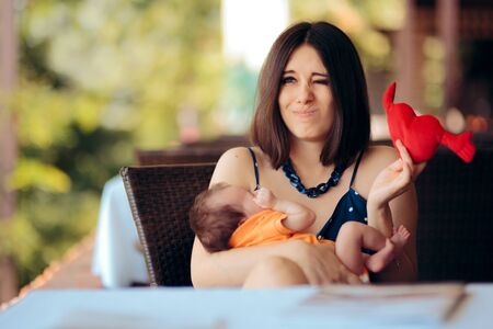 Mother Holding Toy Calming her Crying Baby in a Restaurant