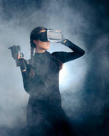 Frau mit einer Waffe mit VR-Brille-Headset
