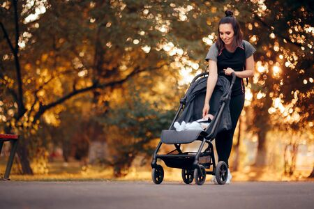 Active Mother Wearing Sporty Outfit Pushing Stroller in the Park