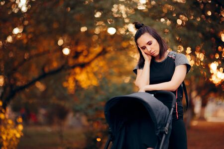Exhausted Mother Having Headaches Pushing a Baby Stroller Stock Photo