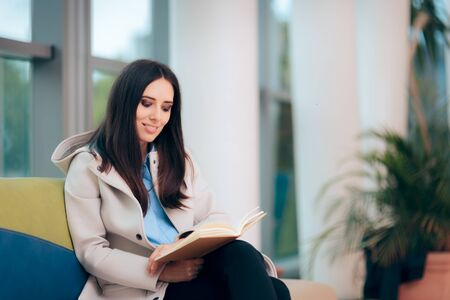 Woman Sitting on a Couch in Waiting Room reading a Book