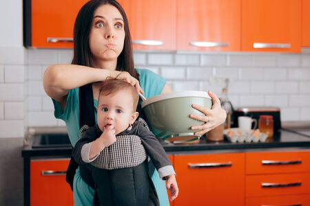 Busy Mom Cooking  Holding Baby in Carrier Babywearing System