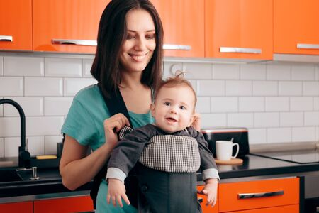 Happy Mother Holding Baby In Carrier in The Kitchen Фото со стока