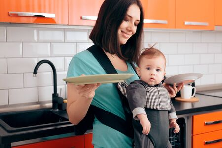 Mother Holding Dishes Holding  Baby in Carrier Фото со стока