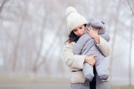 Worried Overprotective Mother Holding baby in Cold Weather Фото со стока