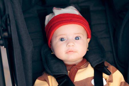 Cute Little Baby Wearing a Hat Seated in Stroller Фото со стока