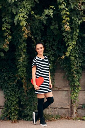 Beautiful Casual Woman Holding a Red Heart Фото со стока