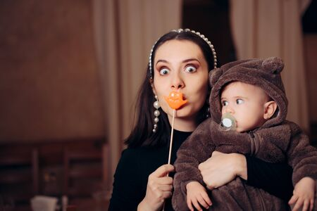 Funny Mother with Party Accessory Holding Baby