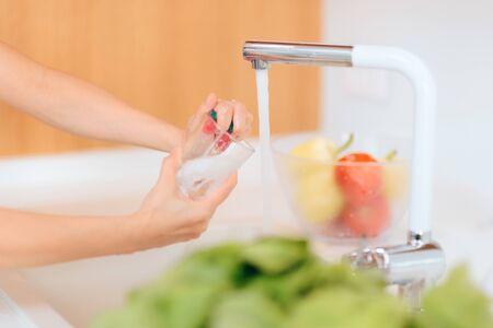 Personne lavant un verre dans un évier de cuisine