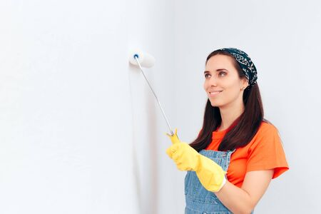 Smiling Woman Painting the Wall at Home with White Paint Foto de archivo
