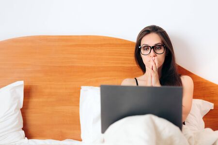Worried Woman Looking at Laptop Sitting in Bed