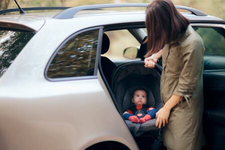 Mother Carrying Newborn Infant in Car Seat Ready for Vacation