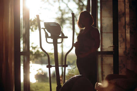 Pregnant Woman Exercising on Elliptical Machine at Home