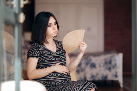 Pregnant Woman Fighting Hot Flushes with a Fan