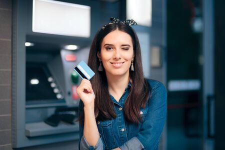 Happy Woman in Front of ATM Machine Holding Card