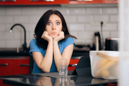 Bored  Woman with Pc Tablet Sitting in the Kitchen