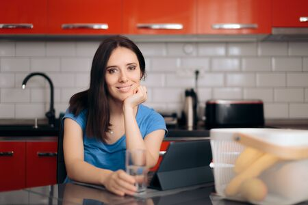 Happy Woman with Pc Tablet Sitting in the Kitchen Standard-Bild
