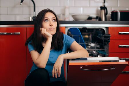 Sad Tired Woman Next to Full Dishwasher Cleaning Kitchen