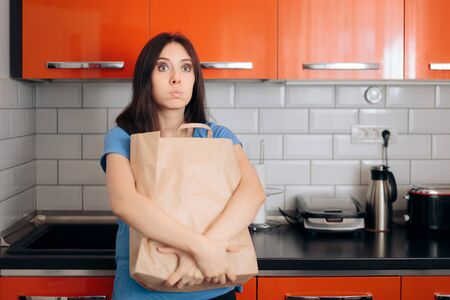 Tired Woman Holding Grocery Bag in the Kitchen Standard-Bild