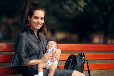 Happy Mother Holding Sleeping Newborn Baby on a Bench