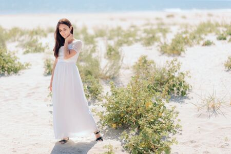 Fashion Woman in Long White Dress on the Beach