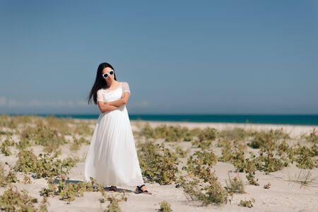 Fashion Woman with Sunglasses Wearing  Long White Dress to the Beach Standard-Bild