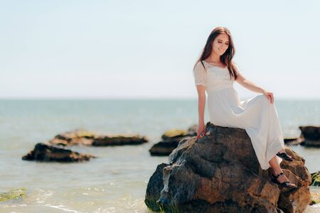 Woman with Long Dress Sitting on Rocks By the Sea