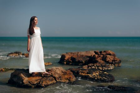 Woman with Long Dress Standing on Rocks By the Sea Standard-Bild