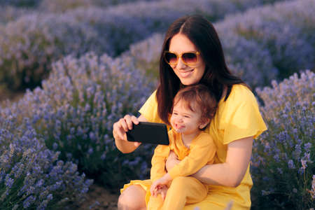 Mother and Baby Taking Selfies in Lavender Field Stock Photo