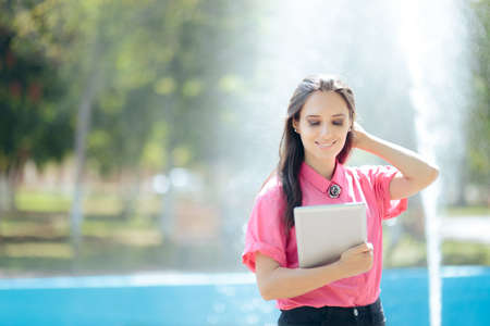 Woman with Pc Tablet in Front of Urban Artesian Fountain