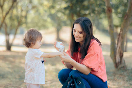 Mother Cleaning Her Daughter Hands with Antibacterial Wipes