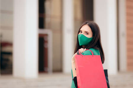 Woman Wearing a Face Mask Holding Shopping Bags Archivio Fotografico