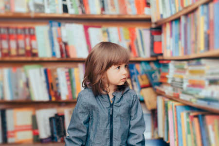 Happy Playful Toddler Girl Standing in a Library Zdjęcie Seryjne