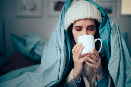 Woman Feeling Cold at Home Drinking Hot Beverage