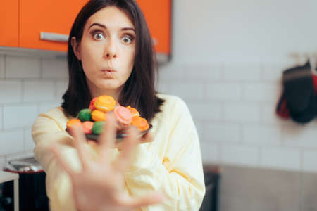 Woman Making Stop Sign Having Macarons by Herself