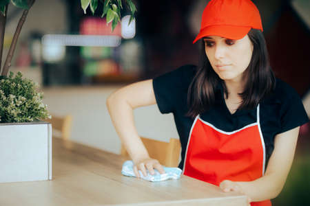 Fast Food Employee Cleaning Tables in a Restaurant