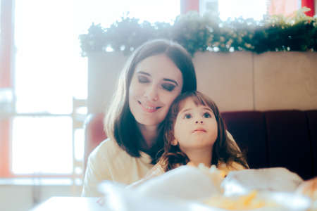 Mother and Daughter Sitting Together in a Restaurant Booth Standard-Bild