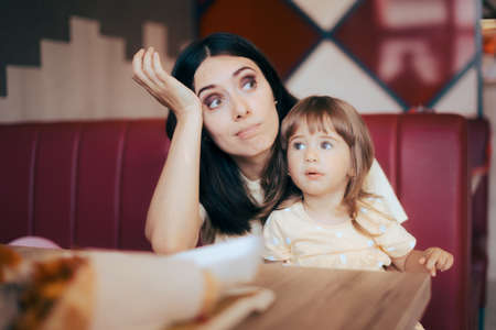 Stressed Mom Sitting with her Child in a Restaurant Booth