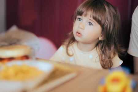 Cute Little Girl Sitting in a Fast-Food Restaurant