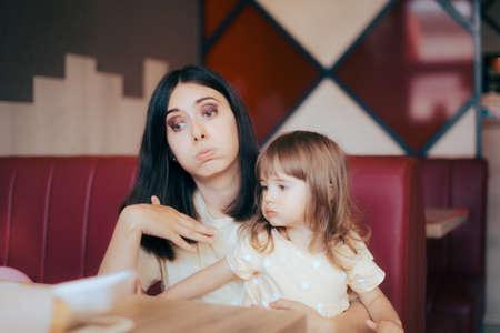 Mom and Child Feeling the Heat Sitting in Indoors Restaurant Standard-Bild