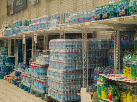 Rimini, Italy, March 21, 2018 shelves of plastic water bottles to shopping center , symbols of huge daily  use of plastic.