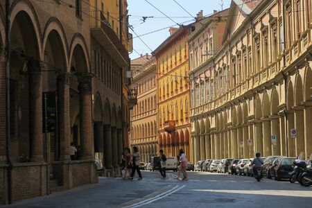 Bologna, Italy - July 4, 2018: People crossing the street in the medieval town, walking from the sunny archs to the shady ones
