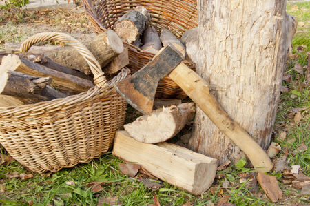 log basket: a lot of chopped wood with an ax lying in a basket on the lawn Stock Photo