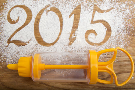 roll out: 2015 inscription on the wooden background with a Confectionery syringe cream Stock Photo